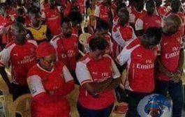 L'imbécilité des Noirs africains : seuls les Noirs africains peuvent se comporter ainsi ; un groupe d'immigrants Nigérians priant pour le succès, la victoire de l'équipe de football (Arsenal FC, d'Angleterre)